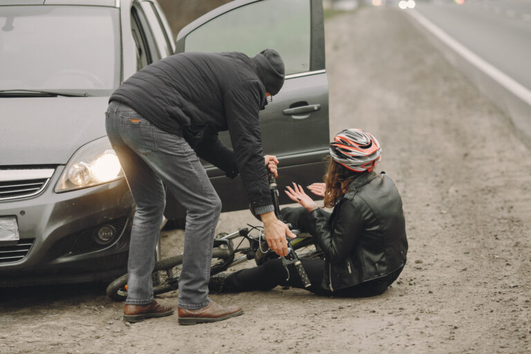 A good samaritan driver stops to help an injured bicyclist on the side of the road.
