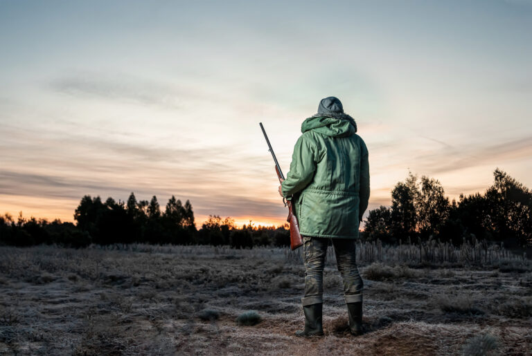 Hunter man in camouflage with a gun during the hunt in search of wild birds or game on a beautiful sunset. The concept of a hobby, killing.