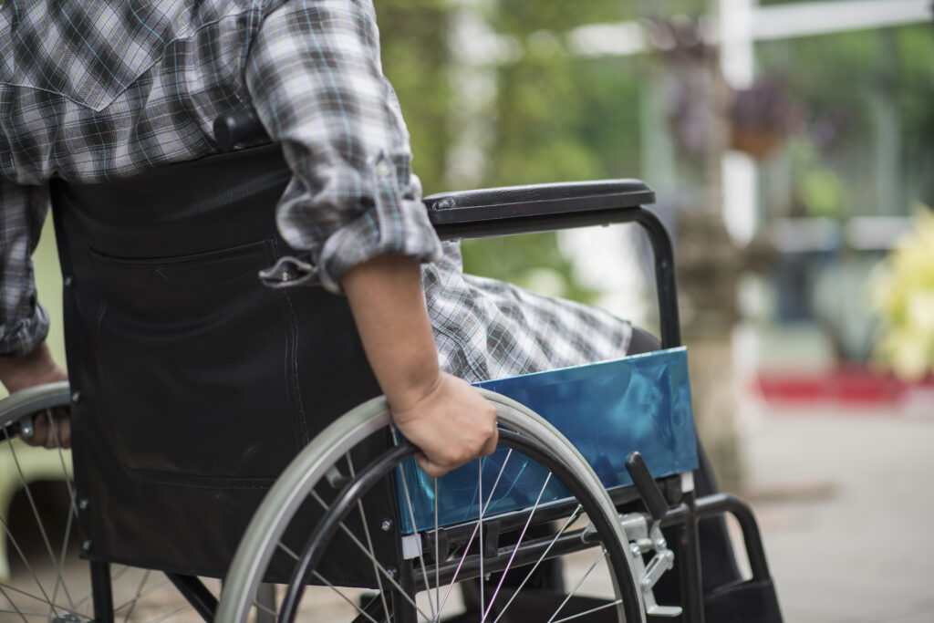 Close-up of senior woman hand on wheel of wheelchair during walk