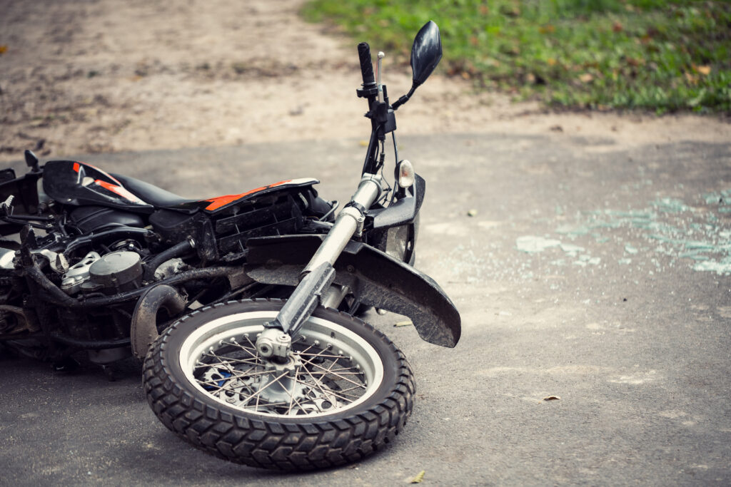 Broken motorcycle on the road after traffic incident