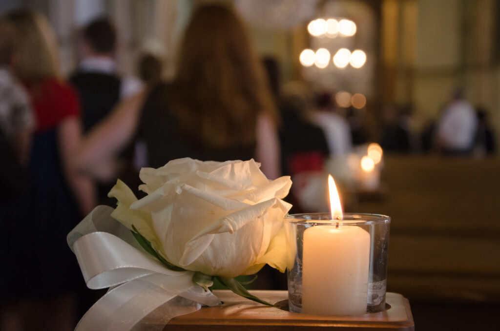 A white rose and a white candle as funeral arrangement in a church