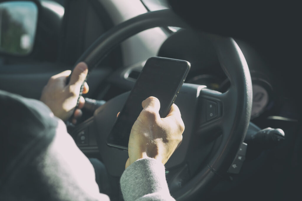 Driver holding a cell phone while driving distracted.