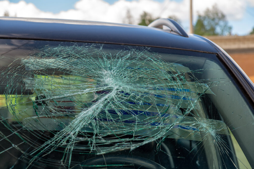 A broken car windshield after a hit and run accident.