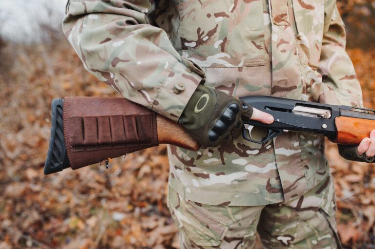 Hunter carrying a shotgun.