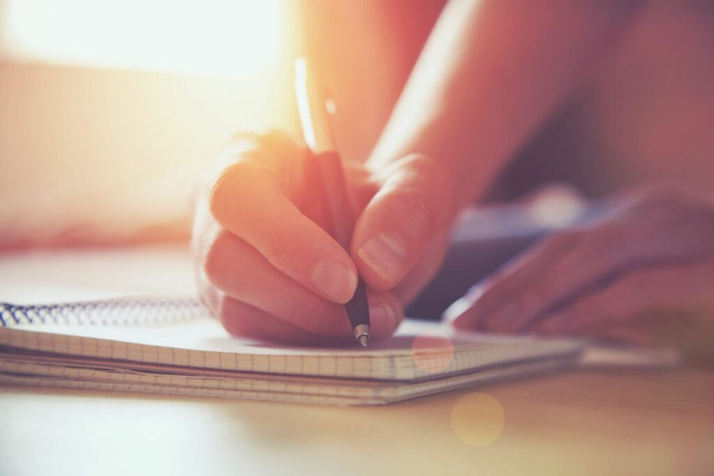 Close up of a woman writing in a journal with a pen.