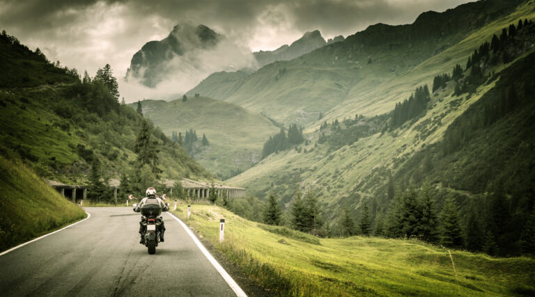 Motorcyclist on a mountainous highway, cold overcast weather,