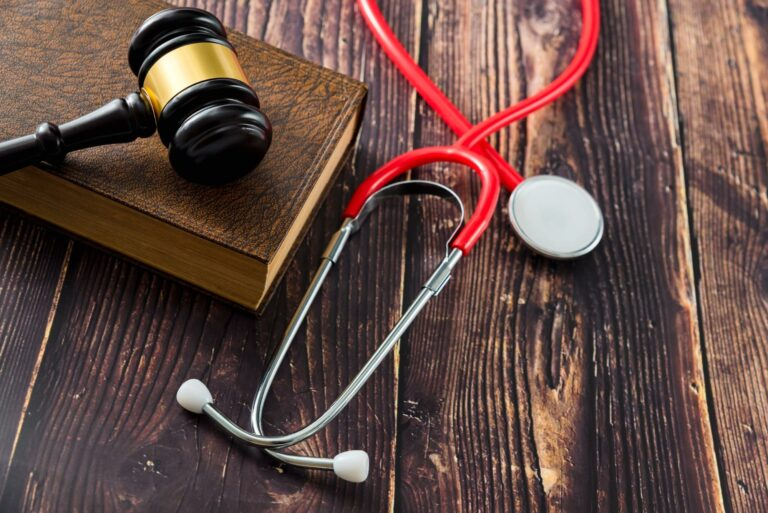 red stethoscope next to judges gavel symbolizing a medical malpractice lawsuit