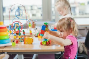 two girls in a daycare playing with small toys which could be chocking hazards without proper supervision