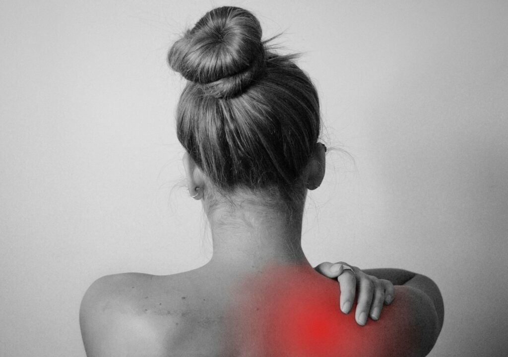 black and white photo of a woman from behind rubbing her right shoulder the center of the pain in her shoulder is highlighted in red