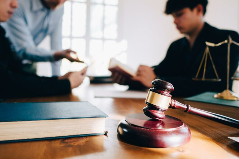 gavel and scales of justice on an attorney's desk as personal injury attorney and client negotiate a settlement with another attorney