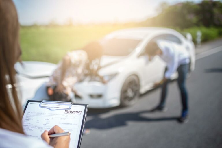 insurance adjuster at the scene of a car accident preparing to take statements from the drivers