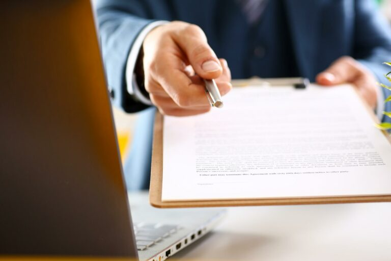 insurance adjuster holding out a pen and clipboard with a low settlement offer for a signature