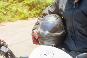 A motorcyclist gets on their bike and prepares to put on their helmet.