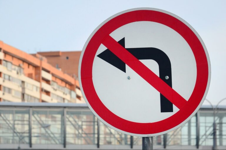 no left turns street sign showing a black arrow pointing left surrounded by a red circle with a red line through the circle