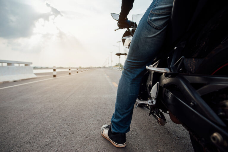 Motorcyclist wearing improper shoes for riding. Proper gear can help protect against foot injuries in a motorcycle accident.
