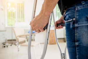 Man's arms walking with crutches