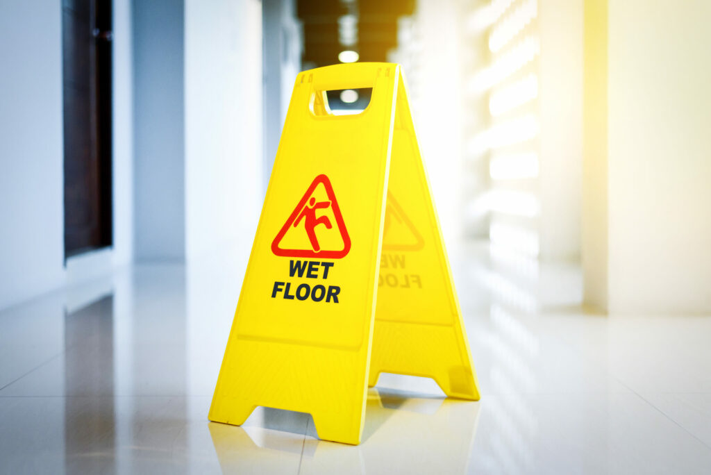 Wet floor warning sign on a tile floor warning people to be careful of slip and fall injuries