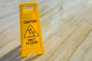Caution sign on a wet floor warning people to look out for slip and fall hazards.