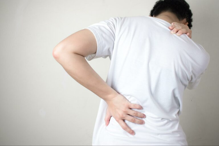 A car accident victim clutches at their neck and back due to the pain caused by aggravated degenerative disc disease.