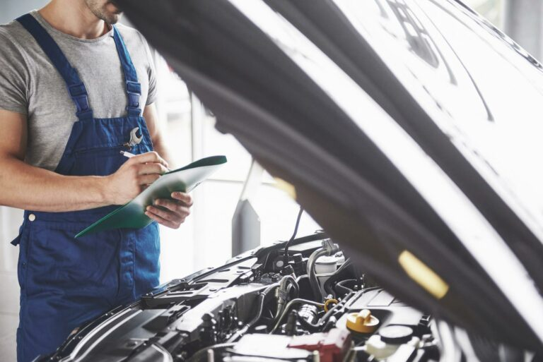 A car mechanic inspects the engine of a car and makes notes on a checklist while performing a required car inspection. Many states have some form of car inspection in order to satisfy registration requirements.