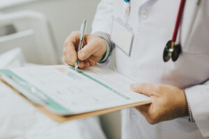 A doctor takes notes with a clipboard while diagnosing a patient with degenerative disc disease which has been aggravated by a car accident.a