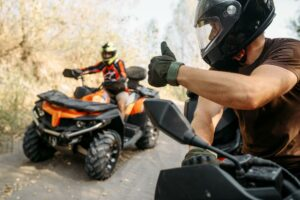 Two ATV operators ride side by side and give each other a thumbs up greeting. Both of the riders are following ATV laws and precautions by wearing helmets and other protective equipment.