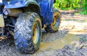 Closeup of muddy ATV tires on a dirt trail. Following ATV laws while out on the trail can keep riders safe when trail conditions are rough.