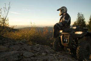 An ATV rider wearing a helmet, boots, and riding coveralls sits on the hood of his parked ATV and takes a break on the trail to look at a beautiful view. Riding an ATV can be a great activity for those who take the proper safety precautions.