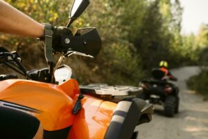 Closeup photo of one ATV rider following another rider along a wooded path. Both of the ATVs are in good condition with the correct safety equipment and the riders are wearing safety gear such as helmets and gloves.