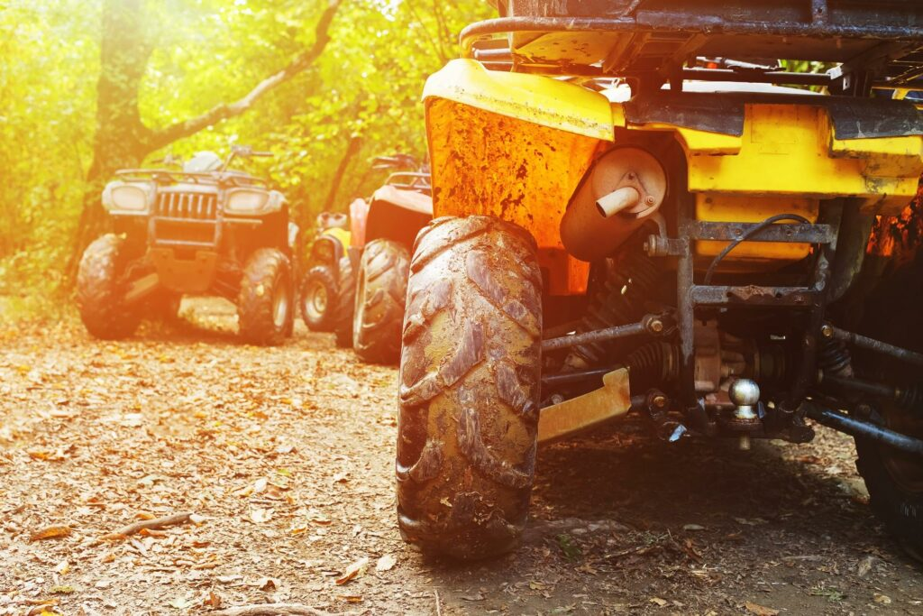 Parked ATVs at the end of a dirt trial in the woods. Following West Virginia's ATV laws can help keep riders safe while having fun on a trail.