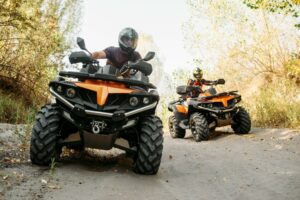 Two ATV riders drive down a dirt path in a wooded area while wearing the proper safety gear including protective helmets.