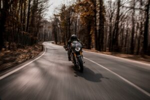 A motorcycles driving up a wooded road at high speed. Speeding on a motorcycle can cause serious or fatal accidents.