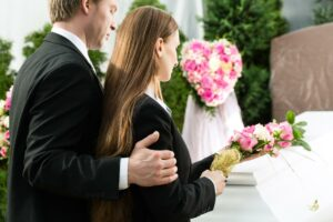 A man and a woman consoling one another at the funeral for a family member. If the death of their family member was the fault of another person, they may be eligible to file a wrongful death lawsuit.