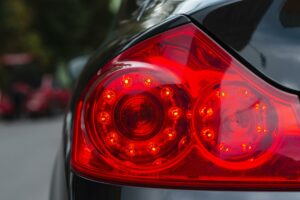 The tail lights of a black car as viewed from behind. Sudden stops are a major cause of motorcycle accidents.