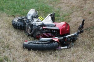 A wrecked motor cycle laying in the grass to the side of a highway after an accident caused by a DUI. Riding a motorcycle while impaired with drugs or alcohol is a common cause of motorcycle accidents.