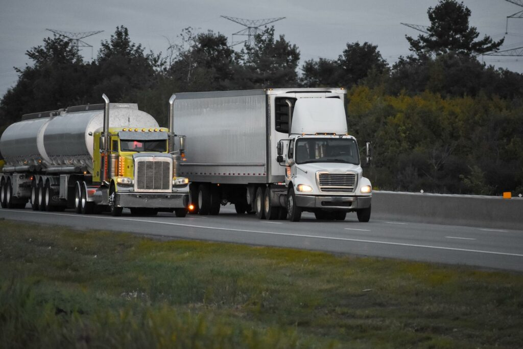 Two semis driving down highway