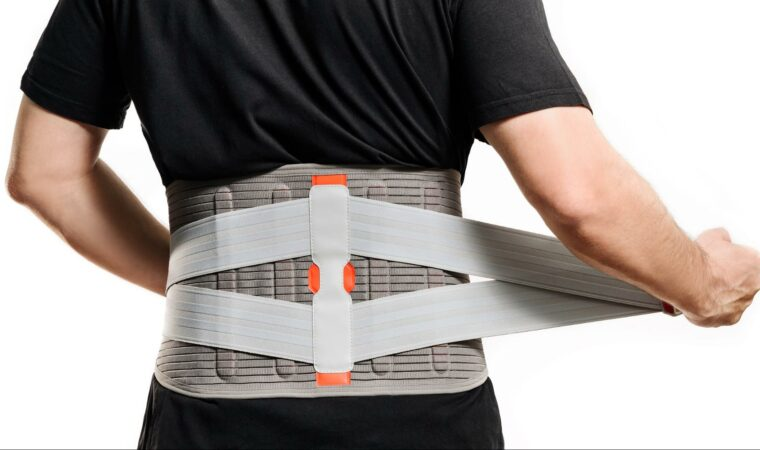 A man who's back was injured in a rear end collision puts on his back brace. Some victims of rear end accidents must wear a back brace or corset as their body heals from their injuries.