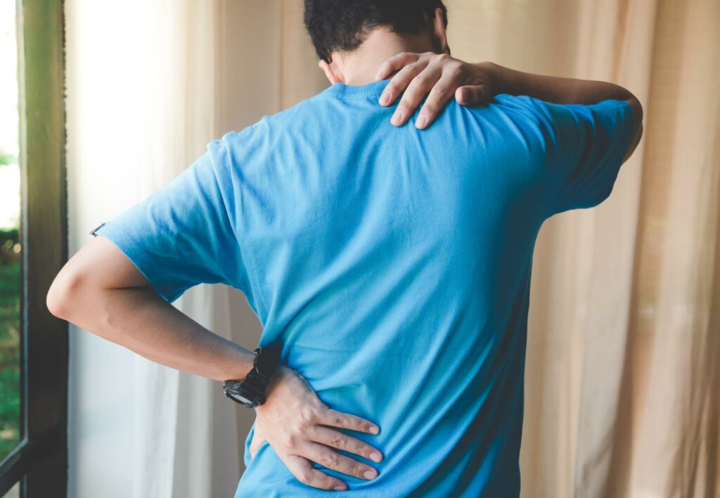 A man who suffered a whiplash injury after a rear end car accident rubs his painful neck and back in an effort to relieve his pain.