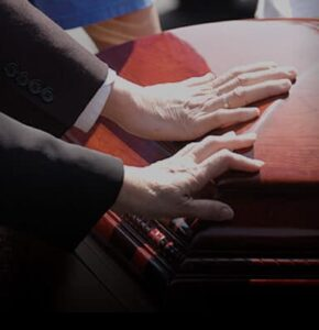 people touching casket