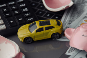 Yellow toy car close-up and dollars bills with broken pink piggy bank. Insurance concept
