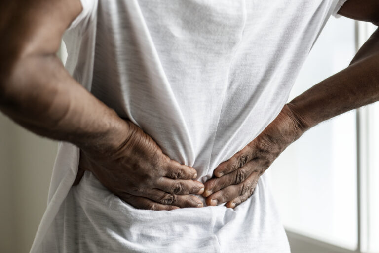 A man touches his sore lower back after suffering a back injury in a car accident.