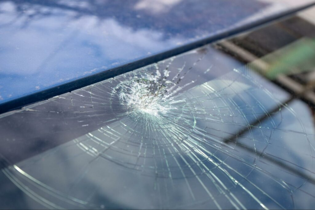A close up photo of a damaged car windshield after an accident.
