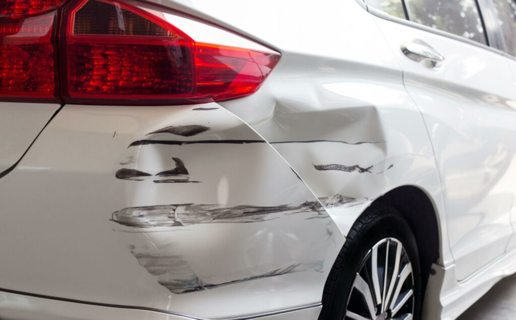 Close up of a car with a damaged bumper after an accident. Contacting a car accident lawyer for even a minor accident can help in getting compensation for car repairs.