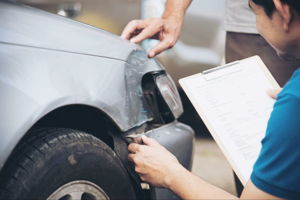A car accident victim and insurance adjuster inspect a damaged car together.