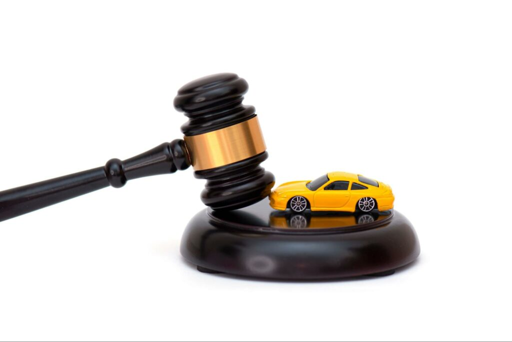 A courtroom gavel and a toy car on a white background. Hiring an attorney to handle a car accident claim is one of the best ways to fight for fair compensation after a car accident.
