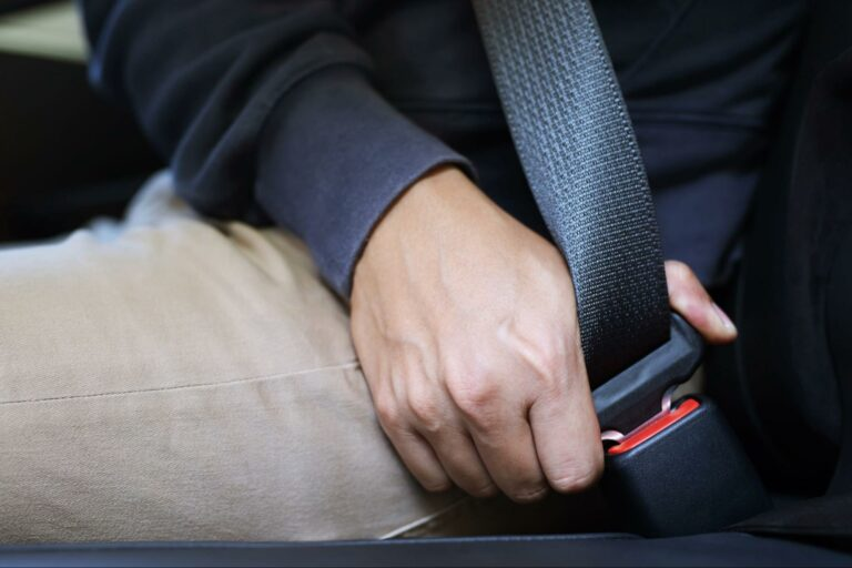 Close up of a passenger in a car buckling his seatbelt.