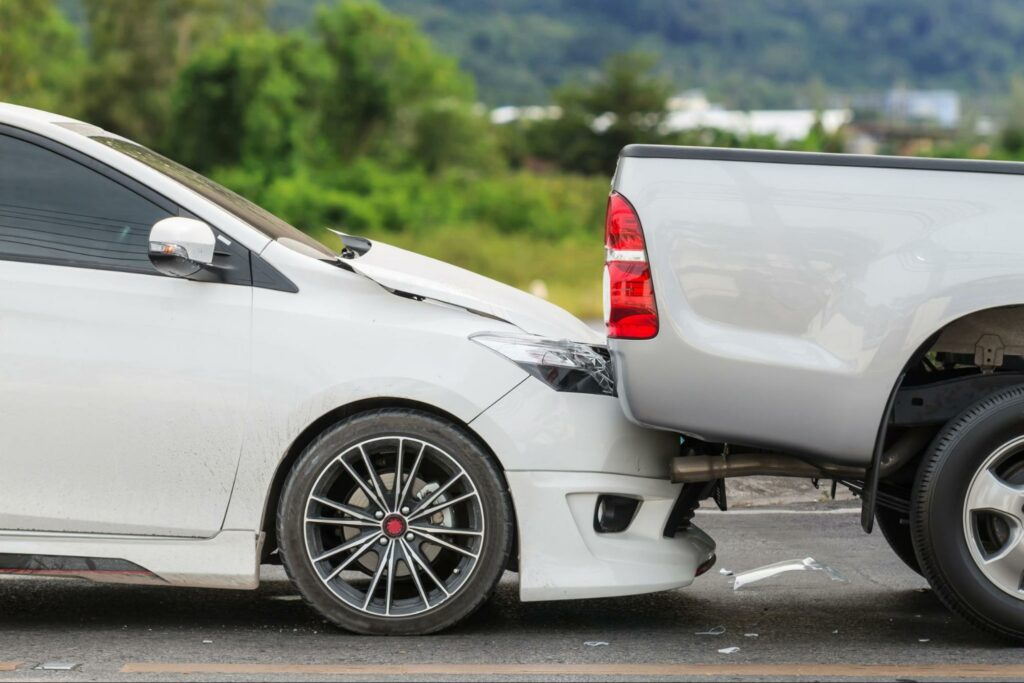 Side view of a rear end accident where a car drove into the bumper of a truck.