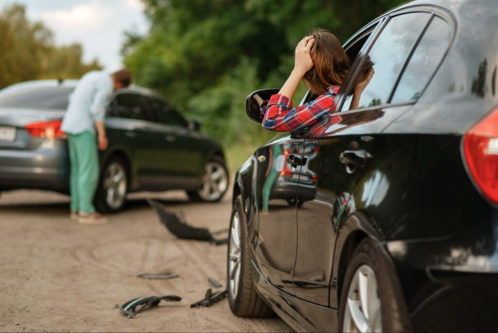 Two drivers inspect their cars after getting into a car accident.