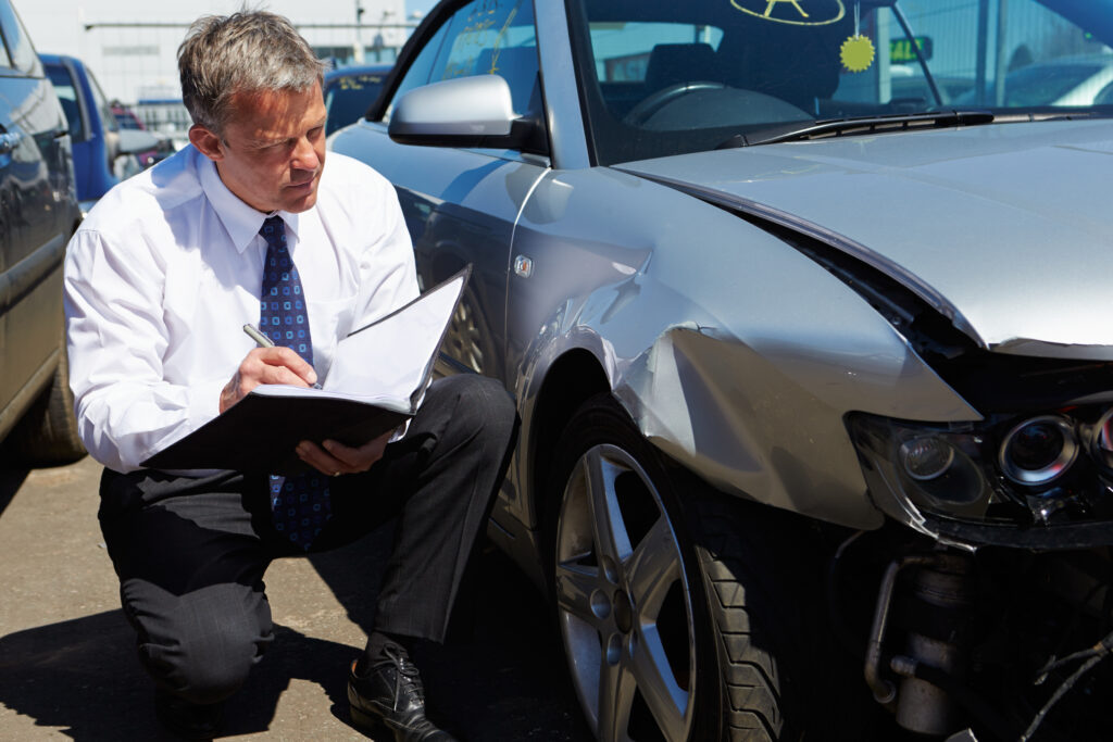 Insurance adjuster looking at car after accident