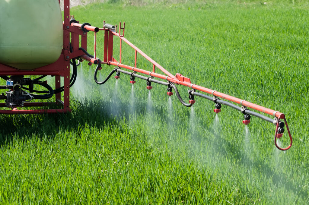 Farm tractor spraying Paraquat herbicide in a field.